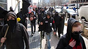 Black bloc - A black bloc group in a feeder march near the World Bank, in Washington, D.C. in 2009. Some black bloc protesters wear hoods, allowing their faces to be viewed, while others use such items as scarves, dark sunglasses or masks to conceal their faces as much as possible.