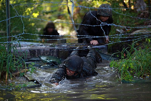 Marines crawl under barbed wire