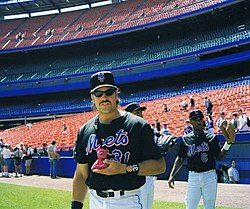 "A man in a black baseball jersey and cap with ""Mets"" across the front in blue script stands on a baseball field."