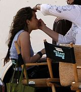 "A side-view shot of a female teenager with long brown hair who smiles as a woman with dark brown hair, glasses, and a white shirt bends to brush the teen's face with make-up. The teen sits in a chair. Beside her is an identical chair with its back facing the camera; the chair's back has the words ""The Last Song"" written across it."