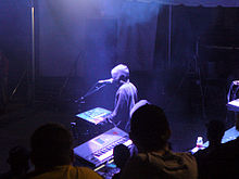 A man with electronic musical instruments performing at an annual electronic dance music event.