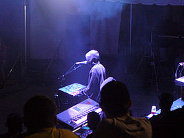 A man with electronic musical instruments performing at an annual electronic dance music event