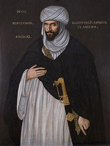 Portrait d'un homme barbu portant une djellaba et un turban blanc avec une tunique noire