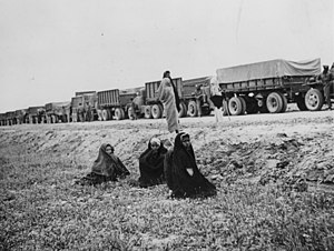 Persian Corridor - Iranian women watch an Allied supply convoy halted somewhere on the Corridor