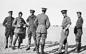 Informal portrait of six men standing in the desert, wearing military uniforms and flying gear