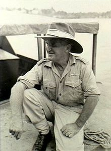 Informal portrait of man in light-coloured military uniform with wide-brimmed hat, crouching on one knee