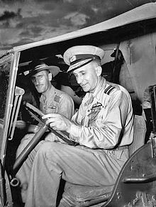 Two men in light-coloured military uniforms sitting in a jeep