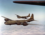 Two large olive-colored aircraft flying over farmland.