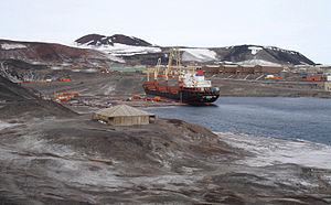 McMurdo Station - The supply ship MV American Tern during cargo operations at McMurdo Station during Operation Deep Freeze 2007. The square building in the foreground is Discovery Hut.