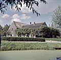 Overzicht van de voorgevel en linker zijgevel van boerderij met dwars aangebouwde houten schuur - Groot-Ammers - 20380566 - RCE.jpg