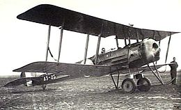Manned single-engined military biplane parked on airfield