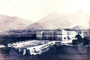 Photograph of a three-storied, neoclassical palace facade, fronted by a large open space supported by massive retaining walls and with high mountains rising in the background