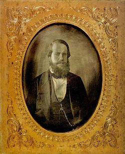 a gold-framed photographic portrait of a bearded man dressed in a dark formal suit with a watch chain hanging from the vest