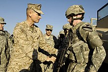 A soldier wearing the SSI of the 1st Cavalry Division speaking with Gen  Peter Pace 1b413d71835