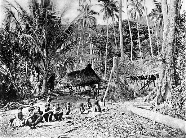Black and white photograph of a village in a forested area.  In the foreground, several men and women sit on the ground.