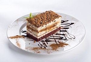 Piece of chocolate cake on a white plate decorated with chocolate sauce.jpg