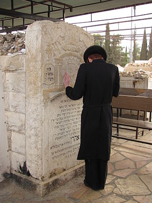 Har HaMenuchot - A man prays at the grave of the Belzer Rebbe.