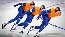 Trois patineurs en combinaison orange, l'un à la suite de l'autre, en fin de virage.