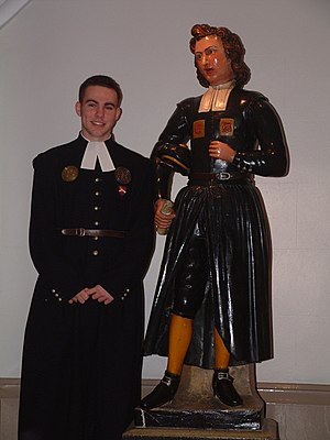 Bluecoat - Queen Elizabeth's Hospital Captain of School 2002/3, dressed in traditional bluecoat uniform, standing by the statue of a pupil in bluecoat uniform.