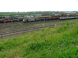 Thornaby TMD - A Mainline-liveried British Rail Class 60 passes westwards through Thornaby with a steel stock service, May 2005. Thornaby TMD can be seen in the back of the picture