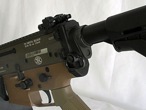 Quick Detach sling mount - An FN SCAR with a black push-button QD sling swivel for attaching a rifle sling near the butt of the riflestock.