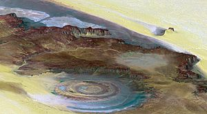 Richat Structure - A topographic reconstruction (scaled 6:1 on the vertical axis) from satellite photos. False coloring as follows: brown– bedrock, yellow/white– sand, green– vegetation, blue– salty sediments.