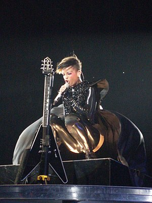 "Last Girl on Earth - Rihanna performing ""Rockstar 101"" with a black guitar in front of her, stylistically reminiscent of particular scenes shown in the song's music video."