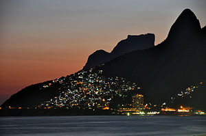 Favela - The lights of Vidigal favela in Rio de Janeiro as seen from Ipanema and Leblon beaches. The cone spire to the far right is part of the Dois Irmãos.