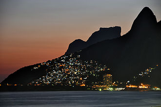Favela - The lights of Vidigal favela in Rio de Janeiro as seen from Ipanema and Leblon beaches. The cone spire to the far right is part of the Morro Dois Irmãos.