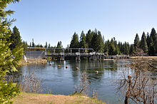 A dam with a metal superstructure creates a placid pool of water behind it. Trees line the banks of the dam pool, which has a string of round markers floating on its surface.