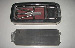 Rolls Razor - Rolls Razor open case. The blade handle on the left is attached to the honing mechanism lever via a spring-loaded bearing. The nickel plated blade on the right side is attached to the honing bar that slides on the red leather strop. The grey honing stone is part of the closing lid. The leather strop and the hone lids are not interchangeable as the blade needs to push against the hone but pull against the strop. The blade has a safety guard with pivot action that allows it to vary the shaving angle while providing safe operation. The head of the blade handle locks perpendicular to the blade using a slide type of action with the spring-loaded bearing providing additional stability