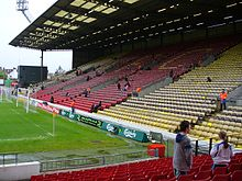 Part of a stadium, consisting of yellow and red seats. A grass football pitch is visible to the left.