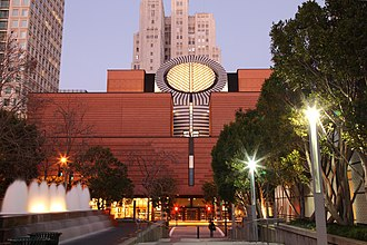 Culture of San Francisco - The red brick and central circular structure of the San Francisco Museum of Modern Art as seen from Yerba Buena Gardens. The Art Deco-style Pacific Telephone Building (1925) rises behind the museum.