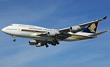 A large mostly-white four-engine jet airliner with golden stylized bird design, on approach towards left of screen with landing gear extended