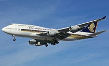 Um grande avião a jato de quatro motores quase branco com design de pássaro estilizado dourado, na abordagem para a esquerda da tela com o trem de pouso estendido