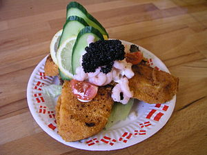 Smørrebrød - Dark rye bread topped with breaded fish, salad, cucumber, shrimps, black-colored lumpfish roe (sort stenbiderrogn) and tomato.