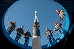 Soyuz MS-11 crew and backup crew at the Soyuz rocket monument behind the Cosmonaut Hotel.jpg