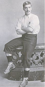 A man with a dark moustache, in a light-coloured football shirt, long dark shorts, and a cap, seated on the edge of a stone balustrade