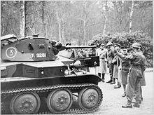 A group of soldiers, including several high-ranking officers, observe a Tetrarch light tank