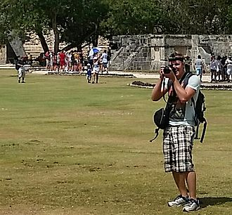 Tourism - A tourist taking photographs and video at an archaeological site