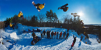 Snowboard - Snowboarder shown at several stages mid-flight.