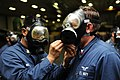 U.S. Navy Logistics Specialist 2nd Class Jeffrey Monzon, left, assists Aviation Structural Mechanic 2nd Class William Cody don a MCU-2P gas mask during a general quarters drill onboard the amphibious assault 111205-N-EK905-073.jpg