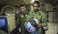 U.S. Navy Lt. j.g. Matt Barrett, left, with Patrol Squadron (VP) 26, watches as an airman with the Royal Brunei Air Force inspects a cranial helmet during a tour of a P-3C Orion aircraft as part of Cooperation 131114-N-KL795-386.jpg