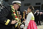 U.S. Navy Rear Adm. Mark Montgomery, left, the commander of Task Force 70, receives a wreath from a child during a welcome ceremony for the aircraft carrier USS George Washington (CVN 73) in Busan, South Korea 131004-N-TB410-008.jpg
