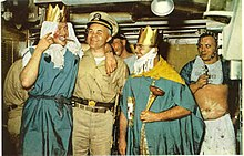 Color photograph of crossing the line ceremony held in the crews mess compartment of the nuclear submarine USS Triton that includes (from left to right) crewman Wilmot A. Jones dressed as the Queen of the Royal Court; Captain Edward L. Beach dressed in khaki uniform and ceremonial sword; Chief Loyd Garlock dressed as King Neptune, Ruler of the Raging Main; crewman Ross MacGregor dressed as Davy Jones in background; and crewman Harry Olsen dressed as the Royal Baby.