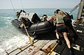 US Navy 030317-N-5319A-011 Members of the Deep-Shallow Water Mark 7 crew from Commander Task Unit (CTU-55.4.3) push their dive boat off the well deck of the USS Gunston Hall (LSD 44).jpg