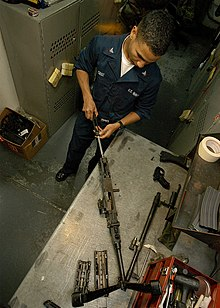 US Navy 040214-N-3986D-001 Aviation Boatswain's Mate Handler 3rd Class Eddy Cruz, of Rochester, N.Y., disassembles a 7.62mm caliber M240B machine gun in the ship's armory aboard the nuclear powered aircraft carrier.jpg