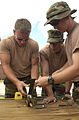 US Navy 040708-N-6811L-068 Machinist's Mate 3rd Class Jeff Nodine, Engineman 2nd Class Mike Hordinski and Hull Maintenance Technician 2nd Class Richard Buschner pack C-4 explosive material into a MK-1 cable and chain cutter.jpg