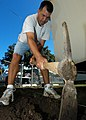 US Navy 050322-N-3019M-002 Navy Region Hawaii Command Master Chief David A. Lajoie levels dirt to the proper elevation for a new sidewalk at Moanalua Elementary School.jpg