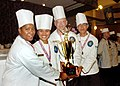 US Navy 060509-N-3560G-062 Culinary Specialist 's Zhou assigned to Naval Mobile Construction Battalion Four (NMCB-4) celebrate capturing 1st place during a competition dinner.jpg